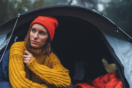 tourist traveler ralaxing in camp tent in froggy rain forest, closeup lonely hiker woman enjoy mist nature trip, green trekking tourism, rest vacation concept camping holiday Stock fotó
