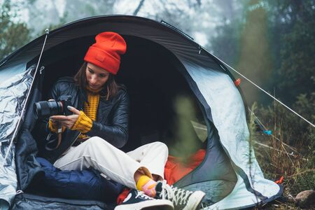 photographer tourist traveler take photo on camera in camp tent in froggy rain forest, hiker woman shooting mist nature trip tourism, rest vacation concept camping holiday Stock fotó