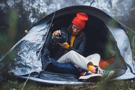 photographer tourist traveler take photo on camera in camp tent in froggy rain forest, hiker woman shooting mist nature trip, rest vacation concept camping holiday