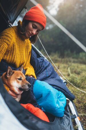 tourist traveler relaxation red shiba inu in camp tent on background blue froggy forest, hiker woman with puppy in mist nature trip, happy friendship love concept, close up
