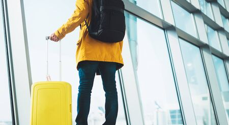 traveler in bright jacket with yellow suitcase backpack at airport on background large window blue sky, passenger waiting flight in departure lounge area, hall of ​airport lobby terminal, vacation trip concept, empty space mockup