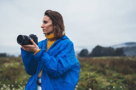 photographer tourist girl in blue raincoat hold in female hands photo camera take photography froggy mountain, traveler shooting autumn nature, video click on camera technology, journey landscape vacation concept free space
