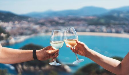 Drink two glasses white wine in friends hands outdoor sea nature holidays, romantic couple toast with alcohol, happy people cheering fun vacation enjoying travel time together friendship love concept congratulations