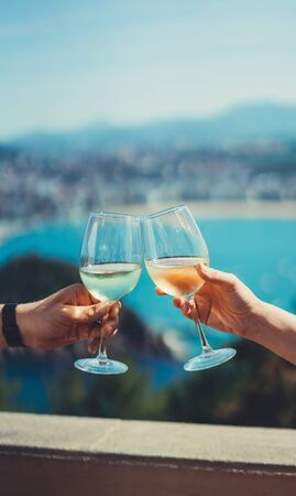 Drink glasses white wine in friends hands outdoor sea nature holidays, two romantic couple toast with alcohol, happy people cheering fun vacation enjoying travel time together friendship love concept congratulations