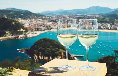 Two drink glass white wine standing on background blue sea top view city coast yacht from observation deck, romantic toast with alcohol panoramic cityscape downtown, spain san sebastian 免版税图像