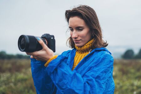 photographer tourist girl in blue raincoat hold in hands photo camera take photography froggy mountain