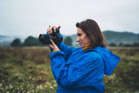 photographer tourist girl in blue raincoat shooting on photo camera froggy mountain