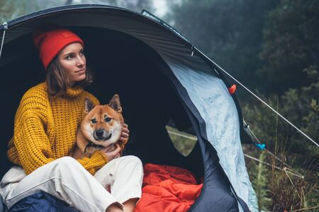 tourist traveler in camp tent hugging red shiba inu on background froggy rain forest, hiker woman with puppy dog in mist nature trip, friendship love concept, relax girl resting dog together