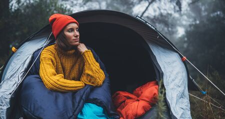 tourist traveler ralaxing in camp tent in froggy rain forest, hiker woman enjoy mist nature trip, green trekking tourism, rest vacation concept camping holiday, campsite active
