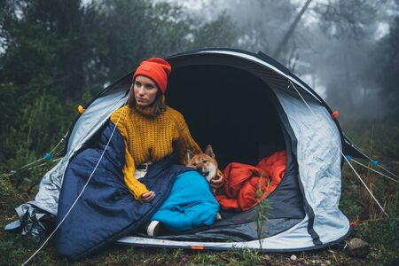 tourist traveler hugging relaxation red shiba inu in camp tent on background froggy forest, hiker woman with puppy dog in mist nature trip, friendship love concept
