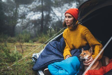 tourist traveler relaxation red shiba inu in camp tent on background froggy forest, hiker with puppy in mist nature trip, friendship love concept, girl resting dog together Zdjęcie Seryjne