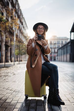 Photographer tourist with suitcase take photo on retro camera. Smiling girl in hat travels in Barcelona. Sunlight street in europe city. Traveler hipster shoot architecture, copy space mockup Zdjęcie Seryjne