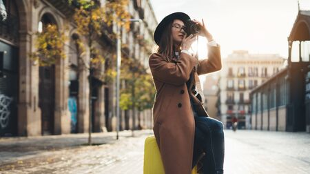 Smiling girl in hat travels in Barcelona. Photographer tourist with suitcase take photo on retro camera. Sunlight flare street in europe city. Traveler hipster shooting architecture, copy space mockup Zdjęcie Seryjne