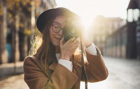 Photographer tourist take photo on retro camera. Girl portrait in hat travels in Barcelona. Sunlight flare street in europe city. Traveler hipster shooting architecture, copy space mockup