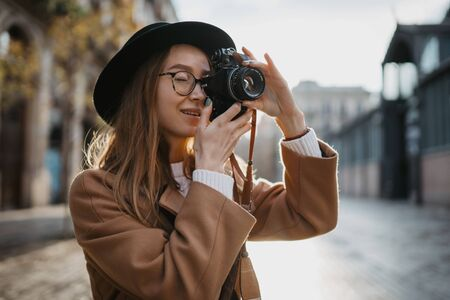 Photographer take photo on retro camera. Tourist portrait. Girl in hat travels in Barcelona holiday. Sunlight flare street in europe city. Traveler hipster shooting architecture, copy space mockup Zdjęcie Seryjne