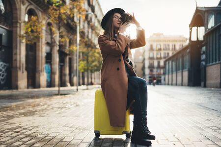 Photographer in glasses take photo on retro camera. Tourist portrait. Girl in hat travels in Barcelona holiday. Sunlight flare street in europe city. Traveler hipster shooting architecture, copy space mockup