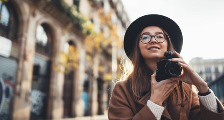 Photographer in glasses take photo on retro camera. Tourist portrait girl in hat travels in Barcelona holiday. Sunlight flare street in europe city. Traveler hipster shooting architecture, copy space mockup