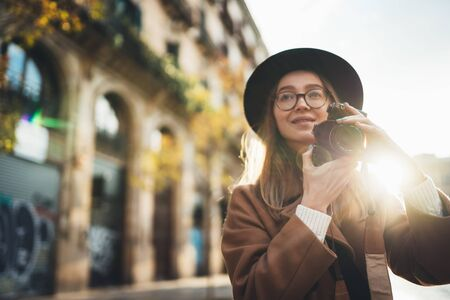 Photographer in glasses take photo on retro camera. Tourist portrait. Girl in hat travels in sun day Barcelona holiday. Sunlight flare street in europe city. Traveler hipster enjoy architecture, copy space mockup