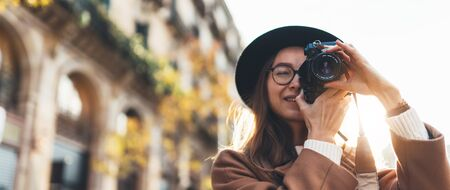 Photographer in glasses with retro photo camera. Tourist portrait girl in hat travels in Barcelona holiday. Sunlight flare street in europe city. Traveler hipster shoot architecture, copy space mockup