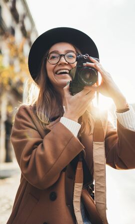 Smiling girl in hat travels in Barcelona holiday. Photographer in glasses with retro photo camera. Tourist portrait. Sunlight flare street in europe city. Traveler hipster shooting architecture, copy space mockup
