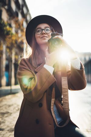 Photographer in glasses with retro photo camera. Tourist portrait girl in hat travels in Barcelona holiday. Sunlight flare street in europe city. Traveler hipster shooting architecture, copy space mockup Zdjęcie Seryjne