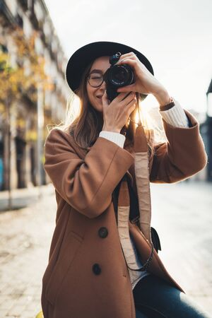 Photographer in glasses take photo on retro camera. Tourist portrait. Girl in hat travels in Barcelona holiday. Sunlight flare street in europe city. Traveler hipster shooting architecture