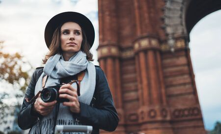 Photographer tourist with retro photo camera. Girl in hat travels in Triumphal arch Barcelona. Holiday concept in europe street. Traveler hipster shoot architecture city, copy space mockup