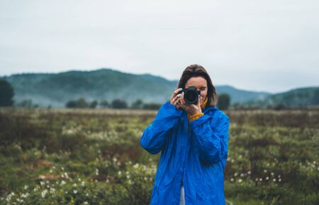 photographer tourist girl in blue raincoat hold in female hands photo camera take photography froggy mountain, traveler shooting autumn nature, click on camera technology, journey landscape vacation concept free space