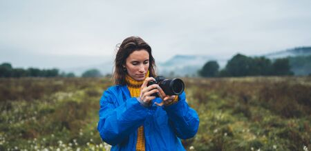 photographer tourist girl in blue raincoat hold in female hands photo camera take photography froggy mountain, traveler shooting autumn nature, click on camera technology, journey landscape vacation concept free space background