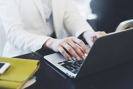 Businesswomen working in office, young hipster manager typing on keyboard, female hands texting message, work process concept in workspace, woman writing text on the open monitor laptop in cafe