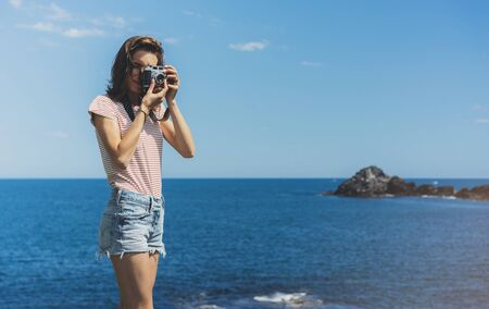 Tourist traveler photographer making pictures sea scape on vintage photo camera on background yacht and boat piar, hipster girl enjoying peak mountain and nature holiday, mockup ocean waves view, blurred backdrop Zdjęcie Seryjne