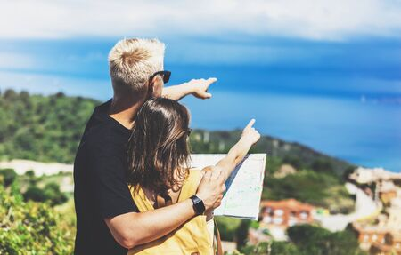 Couple hipster tourist hold and look map on trip, lifestyle concept adventure together, traveler with backpack on background mountain sea landscape horizon, young girl hiker pointing hands on trekking plan