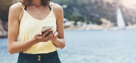 Hipster girl hold on smart phone gadget in sand coastline, mock up blank screen. Traveler using in female hand mobile on background beach seascape horizon. Tourist look on blue sun ocean, summer lifestyle  Zdjęcie Seryjne