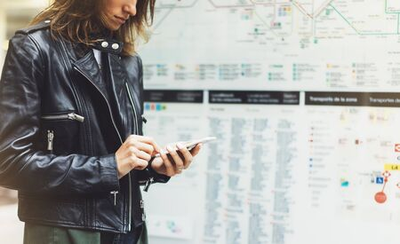 Girl in leather jacket holding smart phone on background map light box in sun atmospheric city, hipster using in female hands and texting mobile, glitter street lifestyle, tourist planing route in summer concept