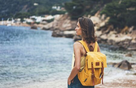 Back view hipster girl with backpack in sand coastline on nature landscape, mock up. Traveler on background beach seascape and horizon mountain. Tourist look on blue sun ocean, summer relax lifestyle Stock fotó
