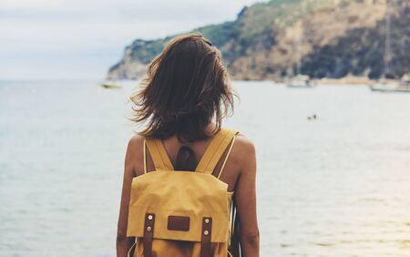 Back view hipster girl with backpack in sand coastline on nature landscape, mock up. Traveler on background beach seascape and horizon mountain. Tourist look on blue sun ocean, summer relax lifestyle  Stok Fotoğraf