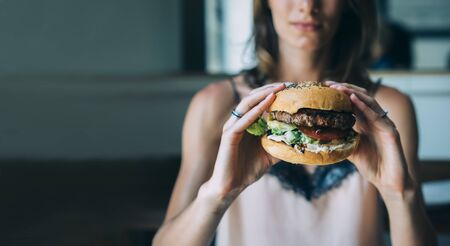 Young girl holding in female hands fast food burger, american unhealthy calories meal on blue background, mockup with copy space for text message or design, hungry human with grilled hamburger front view Stok Fotoğraf - 131957547