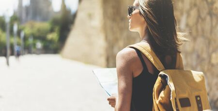 Hipster young girl with bright backpack and fashion sunglasses looking at map. Said view tourist traveler on background sun city. Person visiting the sights Barcelona. Mock up for text message. Zdjęcie Seryjne