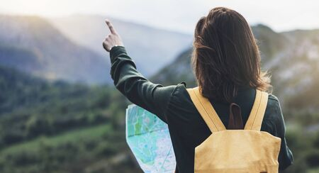 Hipster young girl with bright backpack enjoying sunset on peak of foggy mountain, looking a map and poining hand. Tourist traveler on background valley landscape panoramic view mockup, sunlight in trip in northern spain basque country, mock up for text.