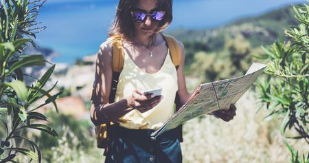 Hipster young girl with bright backpack looking at phone and map. Said view tourist traveler on background mountain, blue sea. Mock up for text message. Female hands using smartphone, holding gadget Stock fotó