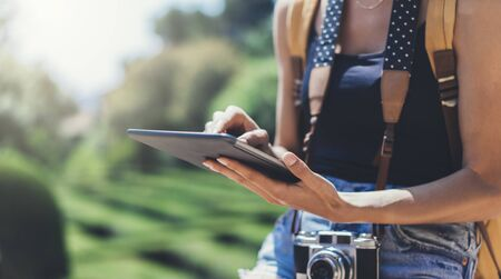 Hipster young girl with bright backpack and vintage camera using tablet or holding gadget, planning travel plan. View tourist traveler with sunglasses on background Parc Laberint Barcelona. Mock up for text message Stockfoto