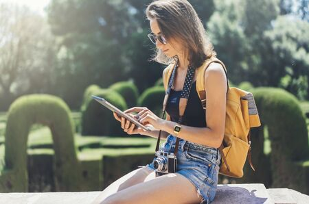 Hipster young girl with bright backpack and vintage camera using tablet or holding gadget, planning travel plan. View tourist traveler with sunglasses on background Parc Laberint Barcelona. Mock up for text message Stock fotó
