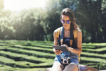 Hipster young girl with bright backpack and vintage camera using tablet or holding gadget, planning travel plan. View tourist traveler with sunglasses on background Parc Laberint Barcelona. Mock up for text message Zdjęcie Seryjne