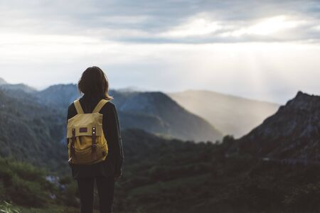 Hipster young girl with bright backpack enjoying sunset on peak of foggy mountain. Tourist traveler on background valley landscape view mockup. Hiker looking sunlight in trip in northern spain basque country, mock up for text. Picos de Europa