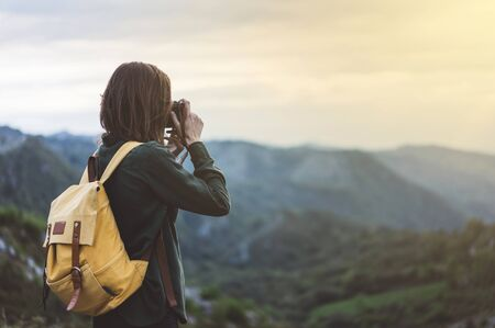 Hipster young girl with bright backpack taking photo of amazing landscape sunset on vintage camera on peak of foggy mountain mockup. Tourist traveler on background sunlight in trip in northern spain basque country, mock up for text.