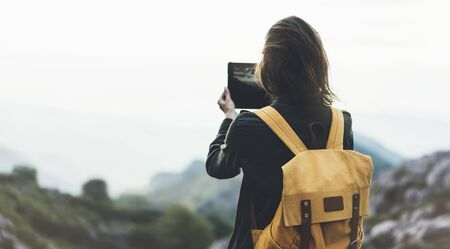 Hipster young girl with bright backpack enjoying sunset on peak of foggy mountain. Tourist traveler on background valley landscape view mockup. Hiker photographing on device in trip in northern spain basque country, mock up for text. Picos de Europa Stock fotó