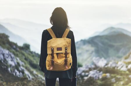 Hipster young girl with bright backpack enjoying sunset on peak of foggy mountain. Tourist traveler on background valley landscape panoramic view mockup. Hiker looking sunlight in trip in northern spain basque country, mock up for text. Girl taking photo of amazing landscape sunset on vintage camera on peak of foggy mountain Standard-Bild