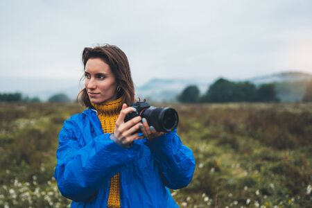 photographer tourist girl in blue raincoat hold in female hands photo camera take photography foggy mountain, traveler shooting autumn nature, video click on camera technology, journey landscape vacation concept free space