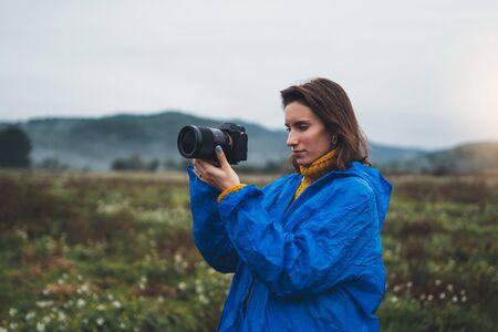photographer tourist girl in blue raincoat shooting on photo camera foggy mountain