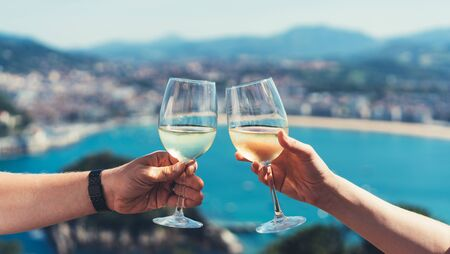 Drink two glasses white wine in friends hands outdoor sea nature holidays, romantic couple toast with alcohol, happy people cheering fun vacation enjoying travel time together friendship love concept blure congrat Stockfoto - 132098024